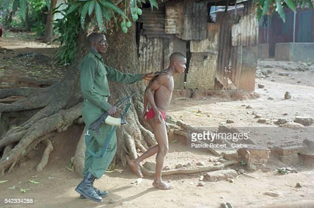 A ECOMOG member arrests a man suspected of being a rebel