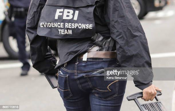 FBI member carries a weapon on the scene where a man driving a rental truck struck and killed eight people on a jogging and bike path in Lower...