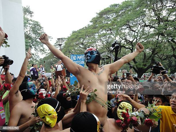 A member from the Filipino fraternity Alpha Phi Omega poses while being hoisted by fellow members of the fraternity in the annual Oblation Run at the...