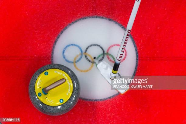 A member from the Japan team brushes the ice in front of the stone during the curling women's bronze medal game between Japan and Britain during the...