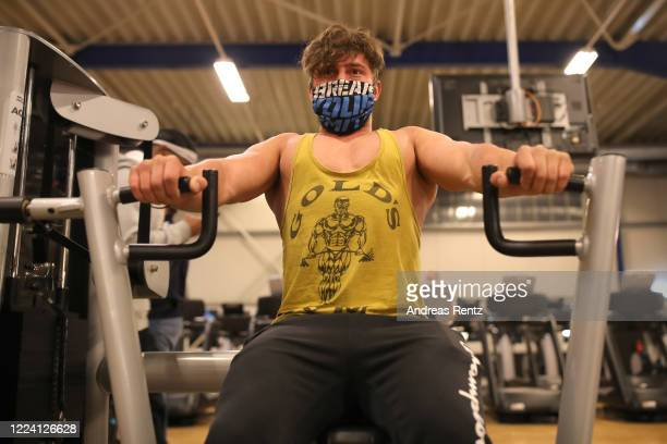 Member Hassib exercises on a fitness machine during his fitness training at a McFit training studio branch after midnight during the coronavirus...