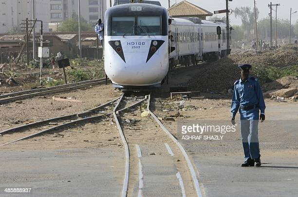 A member o Sudan's security forces stands near the tracks as the new Nile Train passes through Khartoum on March 17 2014 In a dilapidated...