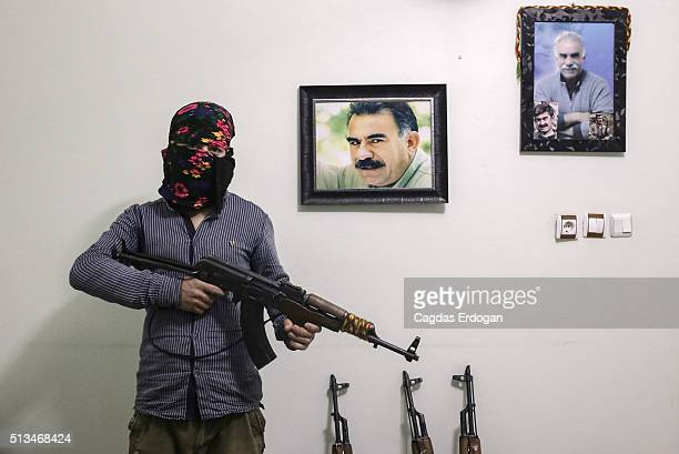 A member of a armed group Patriotic Revolutionary Youth Movement a youth division of the Kurdistan Workers' Party PKK pose with his AK47 next to a...