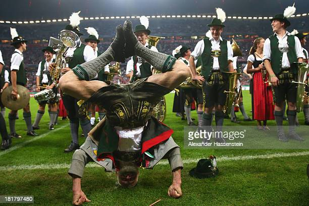 A member of a Bavarian brass band performes a handstand prior the DFB Cup match between FC Bayern Muenchen and Hannover 96 at Allianz Arena on...