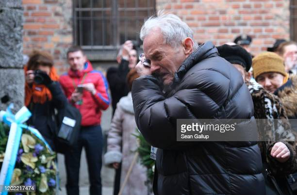 A member of a delegation of survivors of the Auschwitz concentration camp and their families breaks into tears at the execution wall at the former...