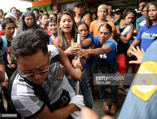 Member of a demolition team tussles with women vendors over a confiscated item, after local government authorities tore down illegal vendors' booths...