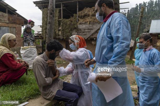 Member of a 'door-to-door' Covid-19 vaccination team inoculates a resident during a vaccination drive at a village in the Budgam district of Jammu...