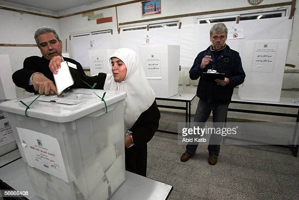 A member of a European Union mission to observe the parliamentary elections in the West Bank and Gaza monitors Palestinians as they vote for the...
