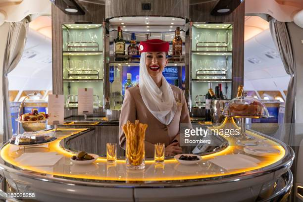 A member of a flight crew stands at a bar in the business class lounge of an Airbus SE A380800 aircraft operated by Emirates Airline during the first...