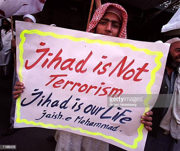 A member of a fundamentalist religious group JaisheMohammad holds up a sign promoting jihad October 16 2001 in Peshawar Pakistan In addition to...