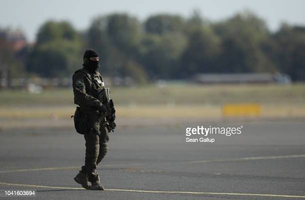 A member of a German antiterror unit stands on the tarmac prior to the arrival of Turkish President Recep Tayyip Erdogan at Tegel Airport on...
