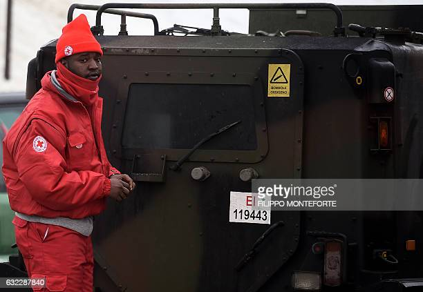 Member of a group of migrants who volunteer with the Italian Red Cross stands at the Penna emergency operations center, some 20 km from the site of...