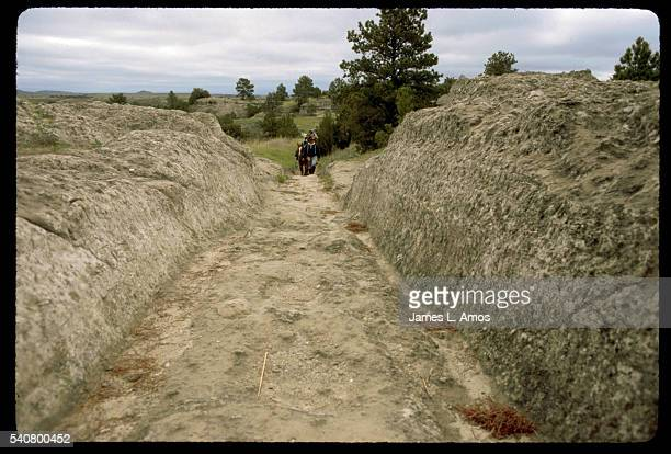 A member of a group riding the Oregon Trail from Fort Laramie to Fort Bridger approaches the Guernsey Ruts ruts worn deep into rock by wagon trains...