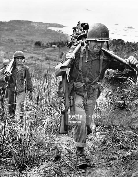 Member of a heavy machine gun crew strains to carry the tripod of his gun up a steep hill on Tinian Island during the Fall of Tinian in World War II....