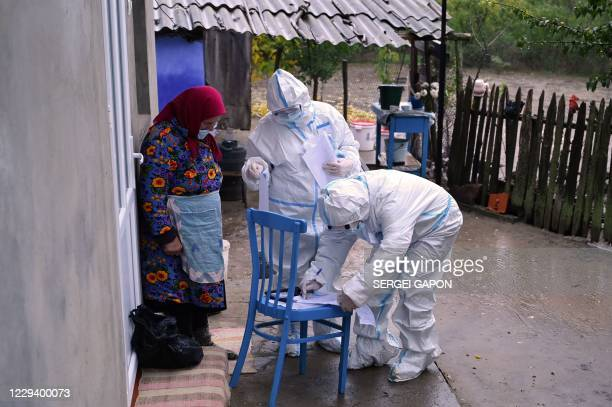 Member of a local electoral commission wearing personal protective equipment fills document as an elderly woman waits to cast her ballot in Moldova's...