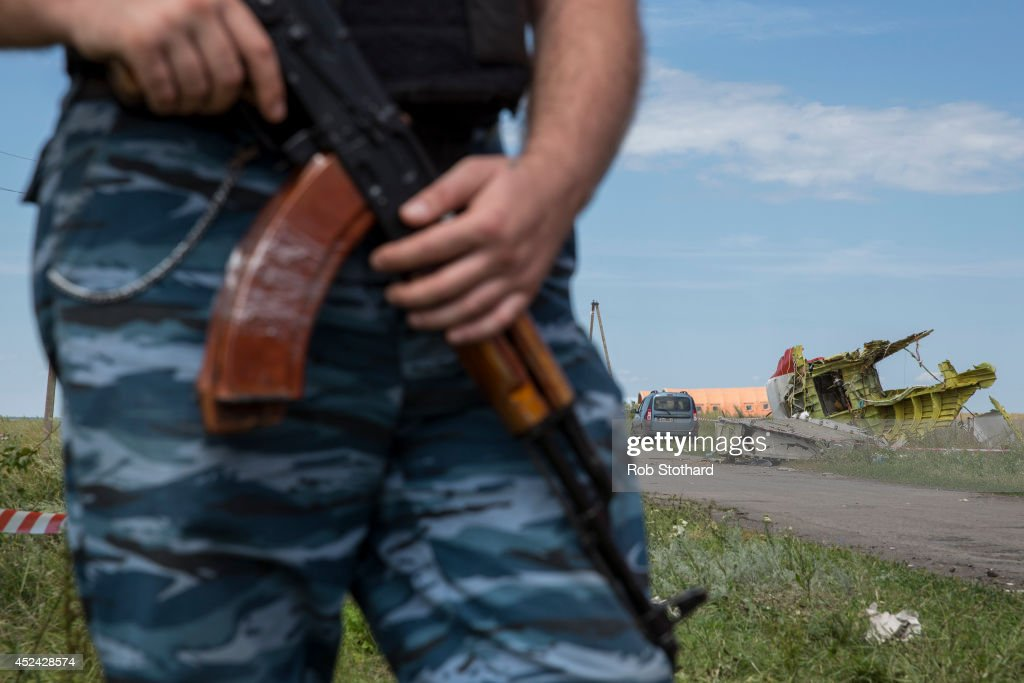 A member of a local militia guards remnants of Malaysia Airlines flight MH17 during a visit by monitors from the Organisation for Security and Cooperation in Europe (OSCE) on July 20, 2014 in Grabovo, Ukraine. Malaysia Airlines flight MH17 was travelling from Amsterdam to Kuala Lumpur when it crashed killing all 298 on board including 80 children. The aircraft was allegedly shot down by a missile and investigations continue over the perpetrators of the attack.