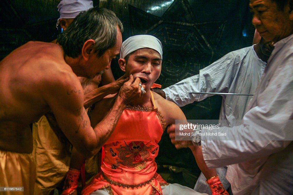 Member of a Malaysian ethnic Chinese community pierces a skewer through a Chinese devotee's cheeks perform a ritual prayer during the Nine Emperor Gods Festival at a temple on October 2, 2016 in Kuala Lumpur, Malaysia. The Nine Emperor Gods Festival welcomes the emperor gods that live in the stars under the reign of 'Thien Hou' or the 'Queen of Heaven' who brings good fortune, longevity and good health. Some devotees stay at a temple during the nine-day Taoist celebration, beginning on the eve of the ninth lunar month of the Chinese calendar, consume vegetarian meals and recite continuous prayers.