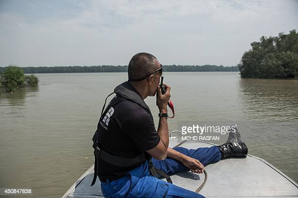 A member of a Malaysian search and rescue team speaks into his walkietalkie during search operations near the area where a boat carrying Indonesian...