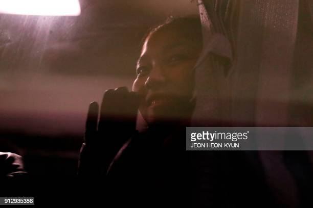 Member of a North Korean delegation of 32 people, including 10 athletes of the North Korean Olympic team, waves from a bus after their arrival at...