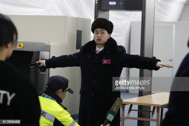 Member of a North Korean delegation of 32 people, including 10 athletes of the North Korean Olympic team, passes through a security check as they...