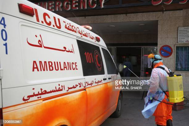 Member of a Palestinian health team in protective gear sprays an ambulance with disinfectant outside the emergency ward of Beit Jala Hospital, on...