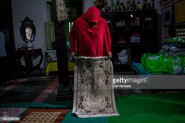 A member of a Pesantren boarding school AlFatah for transgender people known as 'waria' prepares for pray during Ramadan on July 12 2015 in...