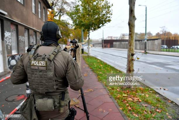 Member of a police commando looks over remains of the Berlin Wall with a sniper rifle at the Berlin Wall memorial, where official guests attended...