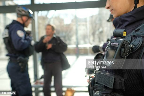 A member of a police patrol conducts a search on a man as one of his colleague stands guard with a body camera attached to the shoulder on February...