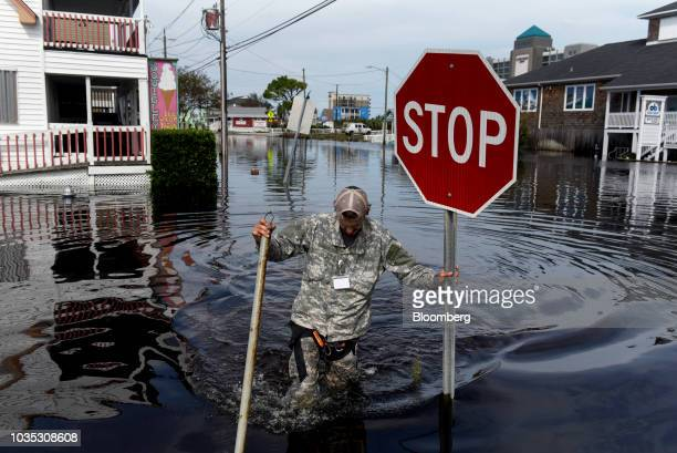 Member of a private critical crisis search and rescue team holds a stop sign as he wades through floodwaters after Hurricane Florence hit in Carolina...