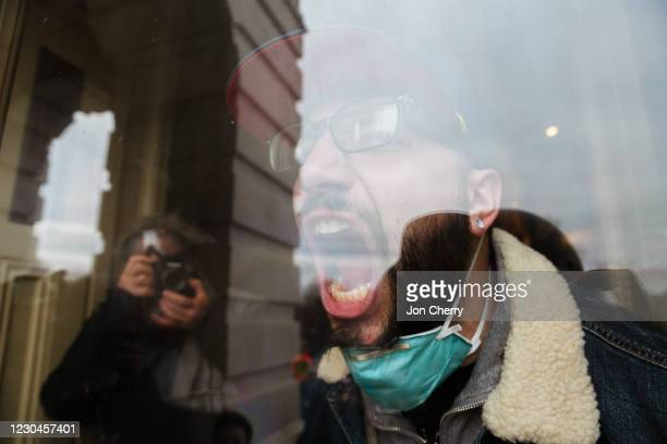 Member of a pro-Trump mob screams out at the crowd from the inside of the Capitol Building after breaking into it on January 6, 2021 in Washington,...