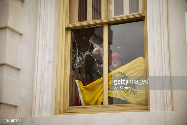 Member of a pro-Trump mob shatters a window with his fist from inside the Capitol Building after breaking into it on January 6, 2021 in Washington,...