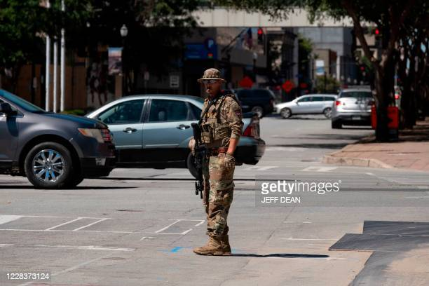 Member of a right wing patriot militia blocks traffic as other members march in downtown Louisville, Kentucky, on September 5, 2020.