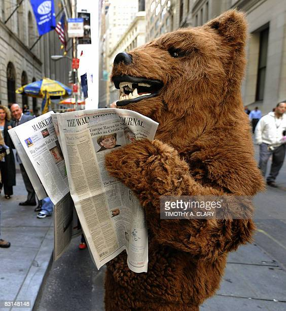 A member of a satire group dressed as a bear to represent a bear market reads a paper outside the New York Stock Exchange on October 6 2008 in New...