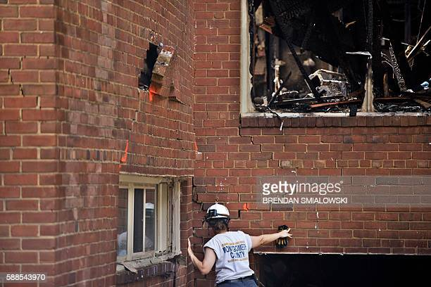 A member of a search and rescue team looks at a damaged wall after an explosion at Flower Branch Apartments on August 11 2016 in Silver Spring...
