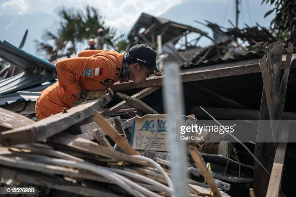 A member of a search and rescue team searches for bodies in the rubble of a building following an earthquake on October 04 2018 in Palu Indonesia The...