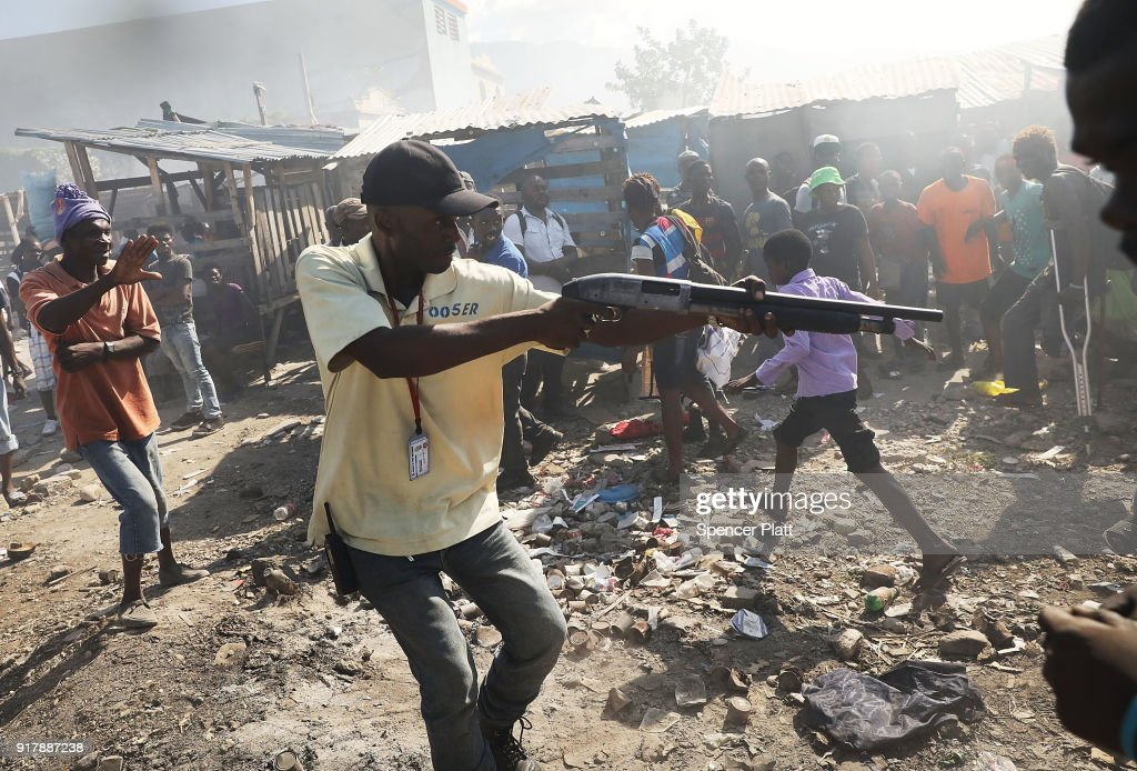 A member of a security force chases crowds with a gun following a fire at Port-au-Prince's historic Iron Market on February 13, 2018 in Port-au-Prince, Haiti. Hundreds of locals vendors lost all of their merchandise in the early morning blaze which is still under investigation. Haiti, the poorest country in the Western Hemisphere, is still reeling from President Donald Trump's comments about the Caribbean nation and his decision to revoke Temporary Protected Status (TPS) for Haitians living in America following the 2010 earthquake that claimed over 300,000 lives. Haiti is currently preparing for the start of Carnival on Sunday.