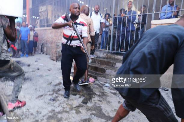 A member of a security force chases crowds with a gun following a fire at PortauPrince's historic Iron Market on February 13 2018 in PortauPrince...