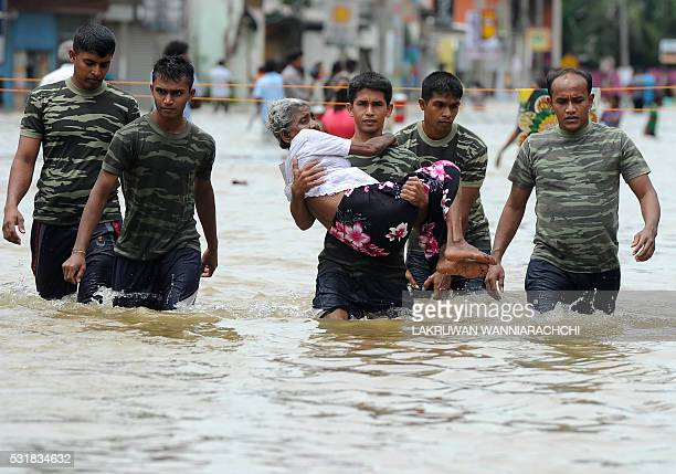 A member of a Sri Lankan Army rescue team carries a woman to safety through floodwaters in the suburb of Kaduwela in capital Colombo on May 17 2016...
