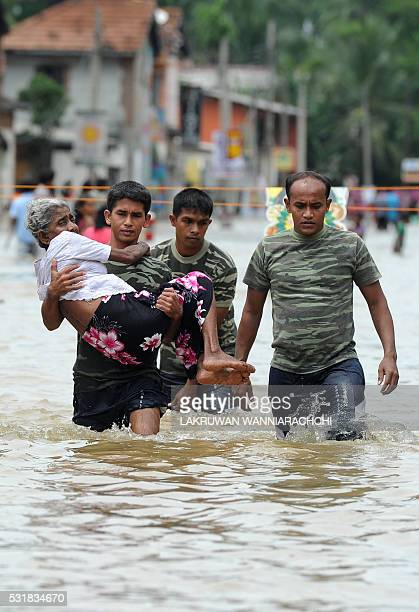 A member of a Sri Lankan Army rescue team carries an elderly woman to safety through floodwaters in the suburb of Kaduwela in capital Colombo on May...