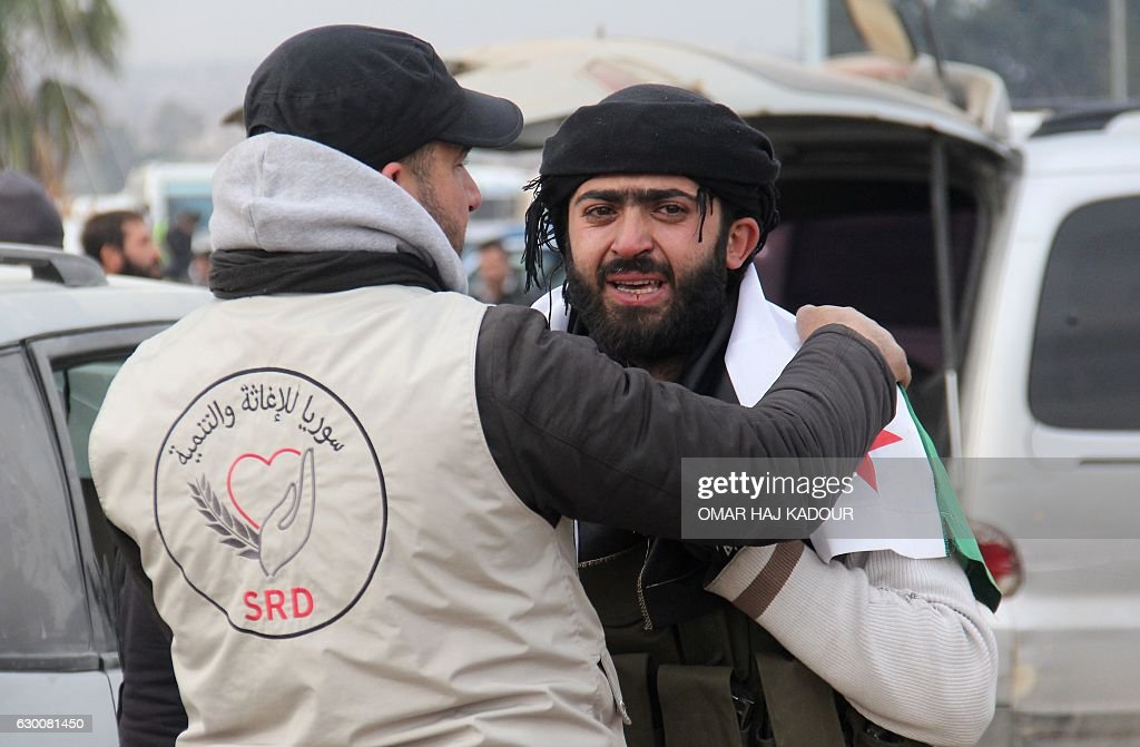 TOPSHOT - A member of a Syrian NGO comforts a man who was evacuated from rebel-held neighbourhoods in the embattled city of Aleppo upon his arrival in the opposition-controlled Khan al-Aassal region, west of the embattled city, on December 16, 2016. The Syrian government suspended the evacuation of civilians and fighters from the last rebel-held parts of Aleppo, leaving thousands of people trapped and uncertain of their fate. The Syrian Observatory for Human Rights, a Britain-based monitor, estimated some 8,500 people had left before the operation was suspended, including around 3,000 rebel fighters. Syrian state media reported a figure of around 8,000. / AFP / Omar haj kadour