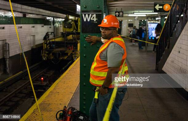Member of a work crew oversees weekend track maintenance at the West 4th subway platform in New York City, New York, September 30, 2017. The New York...