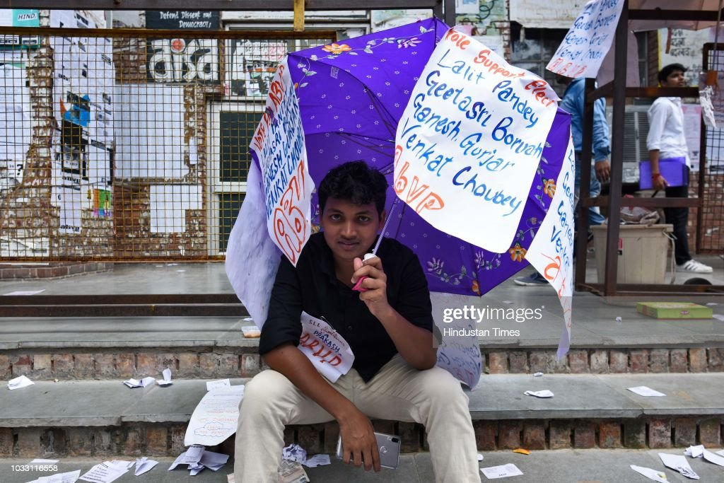 A member of ABVP sits with an umbrella pasted with slogans in support of the candidates during Jawaharlal Nehru University (JNU) Students Union Elections, at the JNU campus, on September 14, 2018 in New Delhi, India. The Left-backed All India Students' Association, Students Federation of India, Democratic Students Federation and All India Students Federation have come together to form the United-Left alliance, which has fielded N Sai Balaji as its presidential candidate. The NSUI has fielded Vikas Yadav for the president's post. The RSS-affiliated Akhil Bharatiya Vidyarthi Parishad (ABVP) has fielded Lalit Pandey for the president's post.