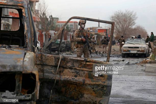 Member of Afghan security force stands guard at the site of an attack in Kabul on December 20, 2020. - A car bomb targeting an Afghan lawmaker killed...