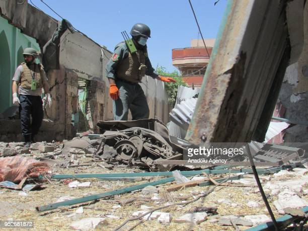 A member of Afghan security forces clears the wreckage near an election registration center after a bomb attack which injured 6 in capital of...