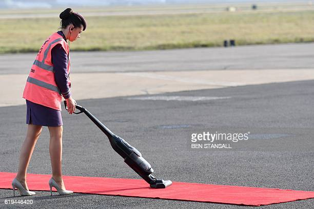 A member of air crew vacuums the red carpet ahead of the arrival of Colombian President Juan Manuel Santos and his wife Maria Clemencia Rodrigue at...