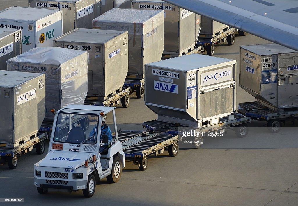 A member of All Nippon Airways Co.'s ground staff drives a cart transporting luggage containers at Haneda Airport in Tokyo, Japan, on Wednesday, Jan. 30, 2013. ANA has canceled a total of 784 flights, affecting 74,200 passengers through Feb. 12, since a Jan. 16 incident that led to the global grounding of Boeing Co. 787s, according to figures from the company. Photographer: Akio Kon/Bloomberg via Getty Images
