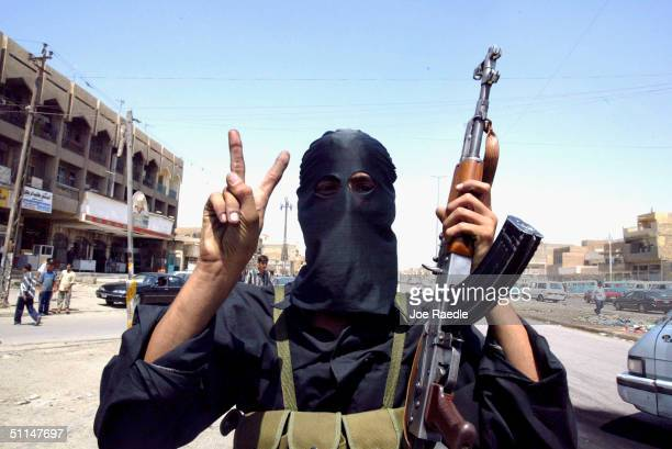 Member of Al-Mehdi army who are loyal to Shiite cleric Moqtada Al-Sadr, flashes the victory sign ahead of a possible battle with US troops August 5,...