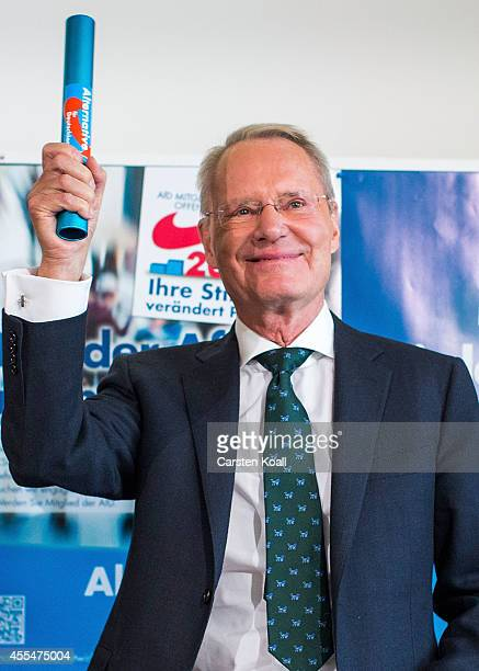 Member of Alternative fuer Deutschland political party HansOlaf Henkel holds a baton during a press conference the day after the AfD finished with...