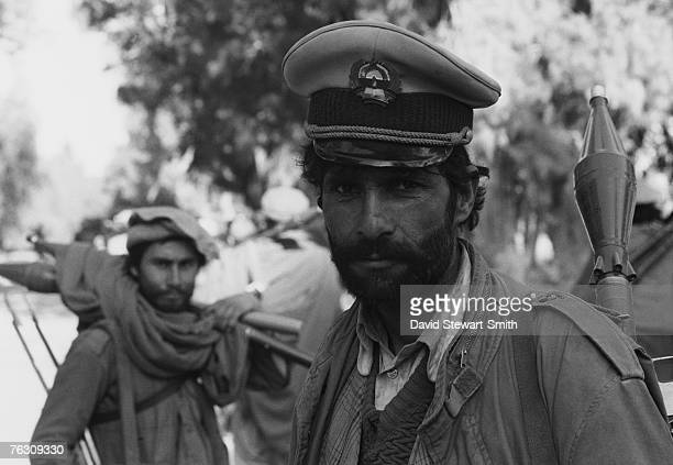 A member of an Afghan Mujahideen group wearing a Soviet military cap during an attack on Jalalabad Afghanistan March 1989 He is armed with an RPG7...