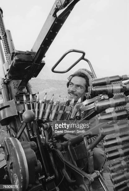 A member of an Afghan Mujahideen group with an antiaircraft gun and ammunition at a camp at Jegdalay in Kabul Province Afghanistan 29th May 1988